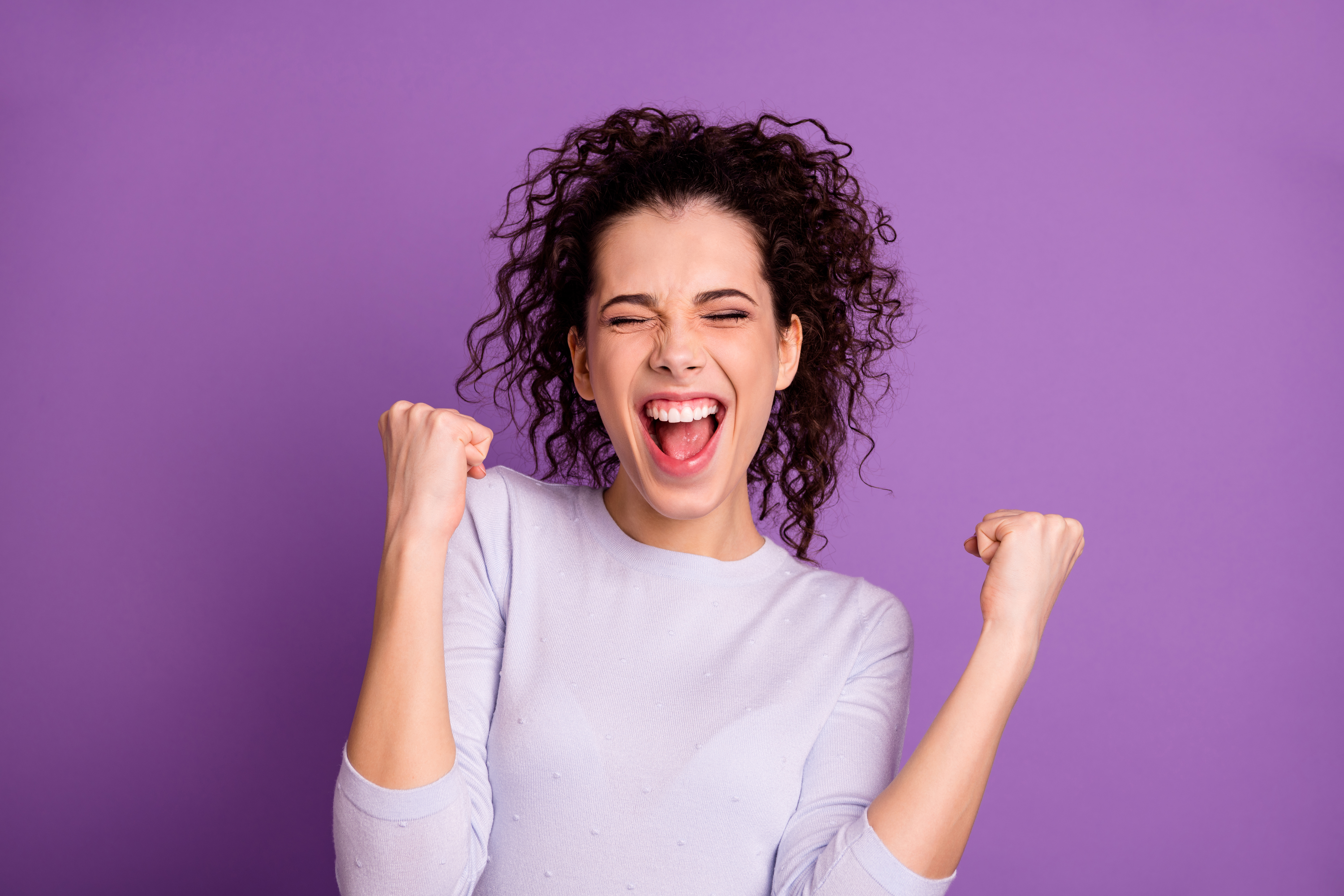 Woman celebrating with eyes closed and fists in the air