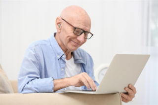A man with a hearing aid uses a laptop